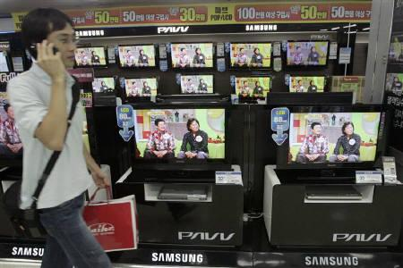 A man walks past Samsung Electronics' LCD TV sets displayed at a shopping mall in Seoul in this August 6, 2007 file photo. Demand for LCD TVs is likely to rise to a fever pitch next year as consumers across the world upgrade their televisions to enjoy the Beijing Olympics games, according to market research firm iSuppli Corp. REUTERS/Han Jae-Ho
