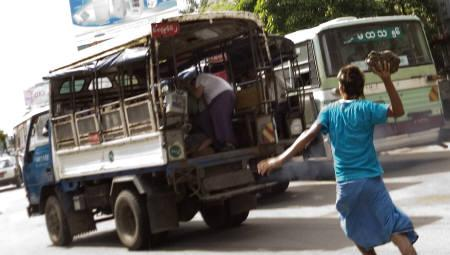 A pro-democracy activist throws a rock at suspected undercover police who drove past a demonstration in Yangon September 29, 2007. REUTERS/Stringer