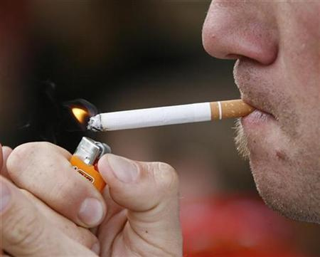 A smoker lights up a cigarette in a public place near the Stade de Geneve in Geneva August 22, 2007. Smoking may turn on some genes in the body in a permanent and harmful way, scientists said on Thursday in a study that may help explain why the risk of cancer remains high even after smokers quit. REUTERS/Denis Balibouse