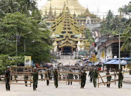 Military officials set up barricades after halting monks from entering the Shwedagon Pagoda in Yangon, September 26, 2007. Myanmar's junta has removed barriers blocking off two Yangon temples that served as rallying points for last week's protests, witnesses said on Monday. REUTERS/Stringer