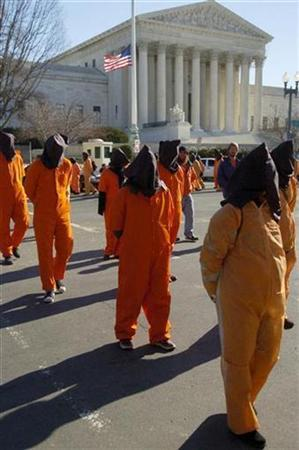In this file photo protesters dressed as prisoners from the U.S. detention facility at Guantanamo Bay march away from the U.S. Supreme Court building in Washington, January 11, 2007. he U.S. Supreme Court began a new term on Monday featuring blockbuster cases on Guantanamo prisoners and the death penalty, and it rejected some 2,000 appeals that had piled up during its summer recess. REUTERS/Jonathan Ernst