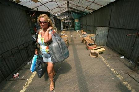 A woman carries bags after shopping in Warsaw in this June 5, 2007 file photo. REUTERS/Kacper Pempel
