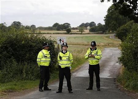 Police officers guard a farm after a suspected case of foot and mouth disease was reported, near Solihull in Birmingham, September 19, 2007. EU vets on Wednesday allowed Britain to resume exports of fresh beef and sheep meat from outside a restricted area in southern England subject to strict conditions, the European Commission said. REUTERS/Darren Staples