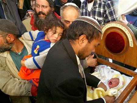 A Jewish settler from the Gaza Strip holds his eight-day-old son at the baby's circumcision ceremony, held in a tent outside Israel's Parliament building in Jerusalem, January 10, 2005. An increasing number of Jews in the United States have decided not to circumcise their sons, rejecting the traditional notion that it is a Biblically prescribed sign of the Jewish relationship with God. REUTERS/Gil Cohen Magen