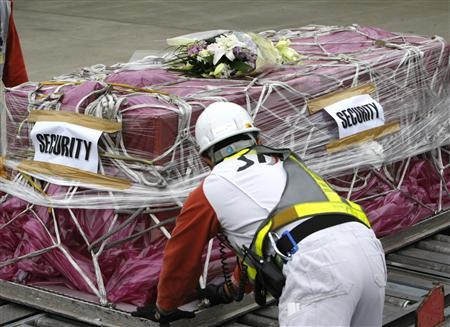 A member of the airport staff unloads the coffin containing the body of Japanese video journalist Kenji Nagai after its flight from Bangkok at New Tokyo international airport in Narita, east of Tokyo, October 4, 2007.REUTERS/Issei Kato