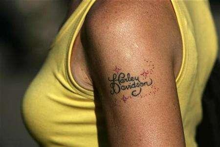 A tattoo is seen on the arm of a Harley Davidson biker at the 16th European Annual Harley Owners Group Rally in Fuengirola, southern Spain, June 21, 2007. Sibu the orang-utan has miffed his Dutch keepers by refusing to mate with females and showing sexual interest only in tattooed human blondes. REUTERS/Jon Nazca
