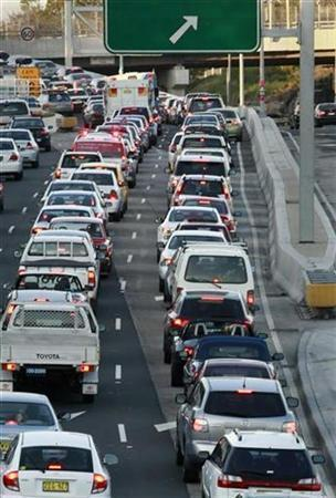 Motorists wait in a traffic jam on a motorway during the evening rush hour as they head out of central Sydney October 2, 2007. The global economic boom has accelerated greenhouse gas emissions to a dangerous threshold not expected for a decade and could potentially cause irreversible climate change, said one of Australia's leading scientists. REUTERS/Tim Wimborne