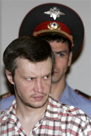 Alexander Pichushkin is followed by a policeman as he enters the courtroom for preliminary hearings at a Moscow court in this August 13, 2007 file picture. A Russian man told a court on Tuesday how he fell in love with killing after his first murder - of a classmate - and admitted to the murder of 60 people, eleven more than he had been charged with. Picture taken August 13, 2007. REUTERS/Alexander Natruskin/Files