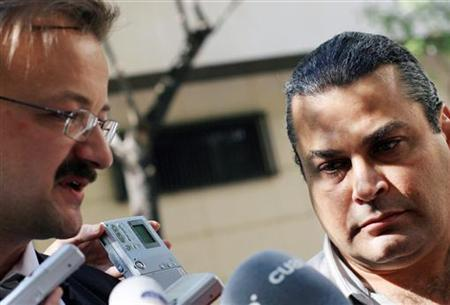 Khaled el-Masri (R) listens to his lawyer Manfred Gnidjic talk to the media after testifying before a judge at Madrid's High Court October 9, 2006. REUTERS/Susana Vera