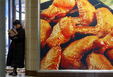 A Chinese woman reads newspaper beside an advertisement for a U.S. fried chicken fast-food chain in Shanghai January 16, 2004. While baseball fans have hot dogs and tennis fans at Wimbledon enjoy strawberries, football fans have claimed chicken wings as their snack, with the demand lifting prices and fueling record sales this year. REUTERS/Claro Cortes IV