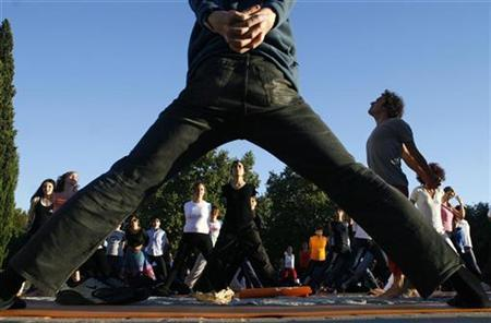 People take part in a free yoga class at the Parque del Oeste in Madrid, September 27, 2007. If a large swath of the population cut down on calories and took up exercise, the resulting health benefits could be extensive, a new study suggests. REUTERS/Susana Vera