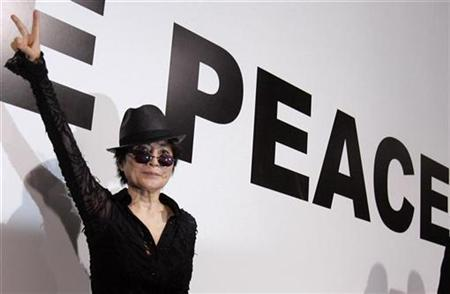 Yoko Ono flashes a victory sign during an opening of her new exhibition 'Odyssey Of A Cockroach' in Moscow, May 29, 2007. REUTERS/Denis Sinyakov