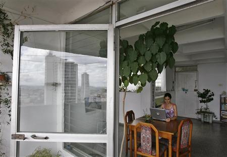 Philology graduate Yoani Sanchez, 32, sits with her computer in her apartment in Havana, October 3, 2007. REUTERS/Claudia Daut