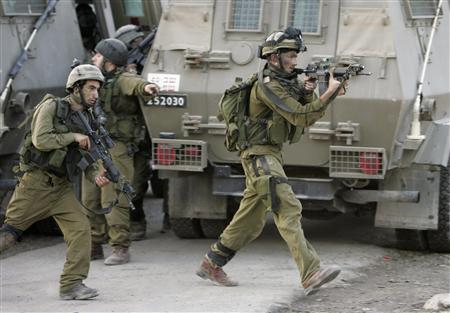 Israeli soldiers take position during a military operation in the West Bank village of Qabatiya near Jenin October 7, 2007. REUTERS/Mohamad Torokman