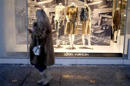 A woman walks past the Louis Vuitton store in New York, February 15, 2007. A woman's online bid to find a rich husband in New York earning more than $500,000 a year has caused an Internet stir with a mystery Wall Street banker publicly assessing her hunt for romance as a business deal -- and a bad one at that. REUTERS/Keith Bedford