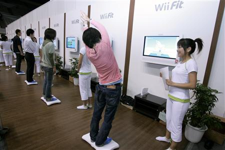 People try out Nintendo Co Ltd's ''Wii Fit'' game console at a media event in Chiba October 10, 2007. Nintendo's hot Wii handheld console is adding a home fitness game to its arsenal before the key year-end gift season, pushing further into the increasingly lucrative health and lifestyle video game segment. REUTERS/Yuriko Nakao