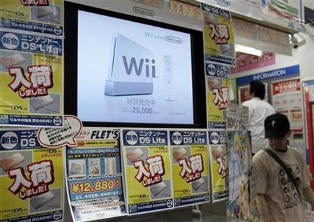 Men walk near a display showing Nintendo's ''Wii'' game console at a game shop in Tokyo's Akihabara electronic district, June 25, 2007. REUTERS/Toru Hanai