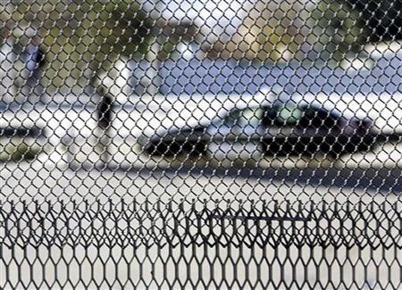 Patrol cars are seen through a fence looking into Juarez, Mexico from the U.S. side in El Paso, Texas, November 29, 2005. Texan mayors on the border with Mexico are threatening to take the U.S. government to court and are encouraging ranchers to do the same to block construction of a fence to keep out illegal immigrants. REUTERS/Jim Young
