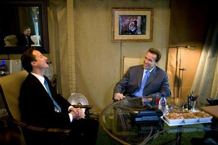 Conservative Party leader David Cameron (L) meets with California's Governor Arnold Schwarzenegger in his smoking tent at the Capitol building in Sacramento October 11, 2007. The Conservatives enjoyed their strongest support for 15 years on Sunday with the latest opinion poll capping a bruising week for Prime Minister Gordon Brown. REUTERS/Kevin German/Pool