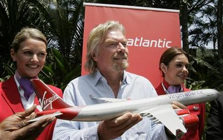 Richard Branson (C), Chairman of Virgin Atlantic Airways, holds a model of an airplane at a news conference in Nairobi March 19, 2007. Branson said on Monday his Virgin Group hopes to produce clean biofuels by around the start of the next decade and early next year will test a jet plane on renewable fuel. REUTERS/Antony Njuguna