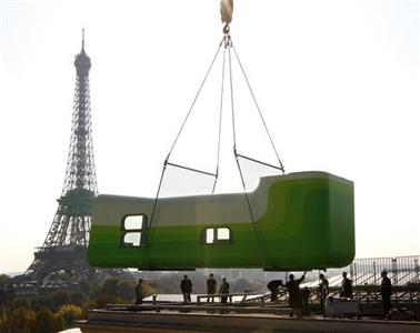 Hotel Everland (C), a creation by Swiss artists Sabina Lang and Daniel Baumann, is lifted onto the roof of the Palais de Tokyo in Paris October 16, 2007. REUTERS/Philippe Wojazer