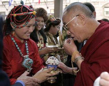 Members of the Tibetan community offer traditional sweet rice to welcome the Dalai Lama as he arrives at his hotel in Washington October 15, 2007. REUTERS/Yuri Gripas