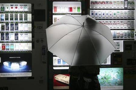 A pedestrian holding an umbrella stands in front of cigarette vending machines as rain falls in Tokyo October 24, 2006. Smokers in Japan will no longer be able to buy cigarettes from vending machines from next year without an ID card that says they are adults under a new system that aims to make it harder for minors to buy tobacco. REUTERS/Issei Kato