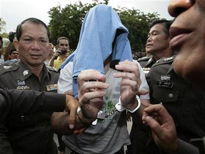 Policemen escort suspected Canadian paedophile Christopher Paul Neil to the national police headquarters in Bangkok October 19, 2007. REUTERS/Sukree Sukplang