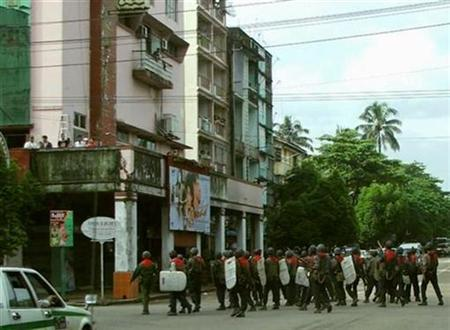 People watch military personnel walking in Yangon, in this September 29, 2007 file photo. Myanmar's military junta lifted a curfew in Yangon on Saturday which was imposed last month after mass protests that prompted a crackdown. REUTERS/Mizzima News