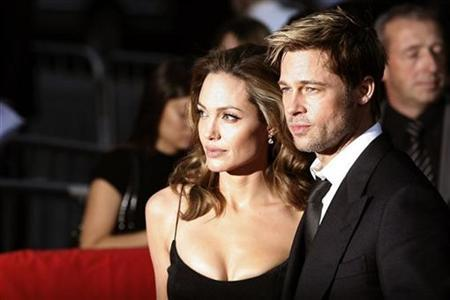 Brad Pitt and Angelina Jolie (L) arrive for the premiere of the film ''The Assassination of Jesse James By The Coward Robert Ford'' in New York September 18, 2007. Jolie and Pitt are making their first joint producing effort with an HBO series about aid workers. REUTERS/Keith Bedford