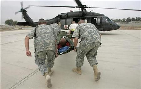 U.S. soldiers rush a patient towards a Medivac Blackhawk helicopter of the Charlie Company 2-227, Aviation Battalion called ''Witchdoctors'' after lading at the forward operating base Liberty camp in Baghdad October 5, 2007. REUTERS/Fabrizio Bensch