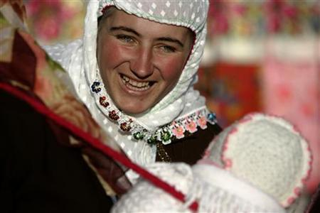 A Bulgarian Muslim woman smiles as she plays with a baby during a wedding ceremony in the village of Ribnovo, in the Rhodope Mountains, November 19, 2006 . Imagine receiving a big chunk of cash in the future. Or winning a prize. Chances are, such optimistic thoughts are coming from two places in the brain that play an important role in enabling people to, as the old song says, accentuate the positive, New York University scientists said on Wednesday. REUTERS/Stoyan Nenov