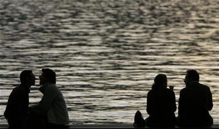 People enjoy a warm autumn evening on the edge of the lake of Zurich, October 5, 2007. REUTERS/Christian Hartmann