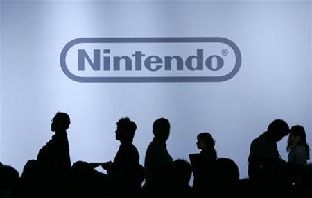 Journalists are silhouetted during Nintendo Co Ltd's news conference in Chiba, east of Tokyo, October 10, 2007. Japan's Nintendo Co Ltd nearly tripled its first-half profit and boosted its annual earnings outlook on Thursday as its popular Wii and DS game machines outsell rival Sony Corp's PlayStation. REUTERS/Yuriko Nakao
