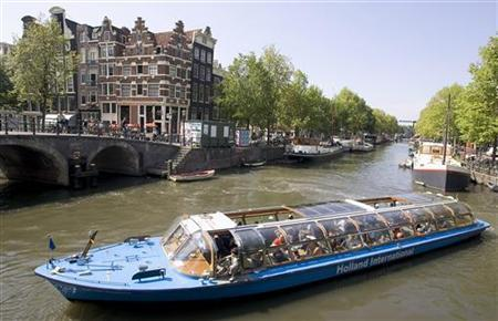 A tourist boat turns from the Brouwersgracht into the Prinsengracht in Amsterdam, August 11, 2004. REUTERS/Michael Kooren