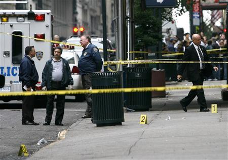 Emergency personnel stand near evidence markers in front of the Mexican Consulate in New York, October 26, 2007. Police were investigating the explosion of two makeshift explosive devices outside the Mexican Consulate in New York on Friday, police said. REUTERS/Jeff Zelevansky