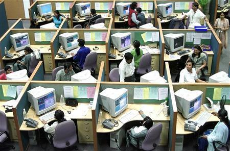 Employees work in an call center in an undated file photo. Work colleagues who spend their day gossiping, organizing their home lives, or who press ''reply all'' on e-mails are among the biggest nuisances in the office, according to a survey released on Monday. REUTERS/File