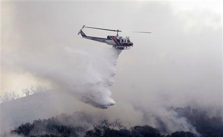 A helicopter makes a water drop as firefighters continue to battle the Santiago fire in Orange County, California, October 27, 2007. REUTERS/Phil McCarten