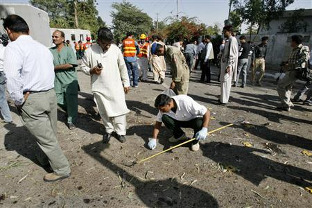 Pakistani police and bomb disposal officials examine the site of a bomb explosion in Rawalpindi, October 30, 2007. REUTERS/Mian Khursheed
