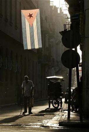 A man walks under a Cuban flag along a street in Old Havana July 17, 2007. The U.N. General Assembly voted overwhelmingly on Tuesday to urge the United States to lift its four-decade-old embargo against Cuba in a resolution adopted for the 16th consecutive year. The measure is nonbinding and such moves in the past have had no impact on U.S. policy. REUTERS/Enrique De La Osa