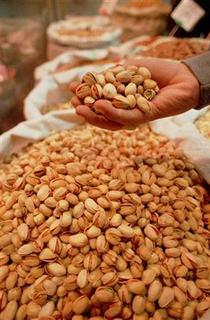 File photo shows a customer grabbing a handful of pistachios at a specialty nuts shop in Tehran, March 17, 2000. Women trying to get pregnant could boost their chances by adopting a ''fertility diet'' high in nuts, according to U.S researchers. REUTERS/Str Old