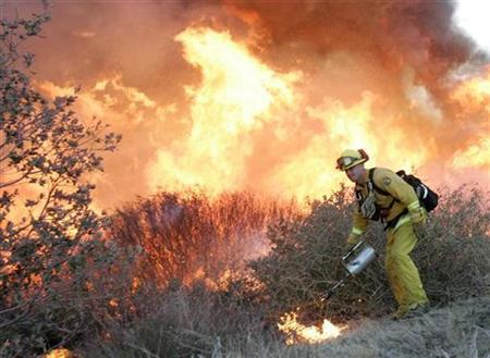 A firefighter sets a burn out as he battles a fire in southern California, October 24, 2007. About two-dozen fires ravaged southern California last week, destroying 2,300 buildings, according to the California Office of Emergency Services. REUTERS/John Gress