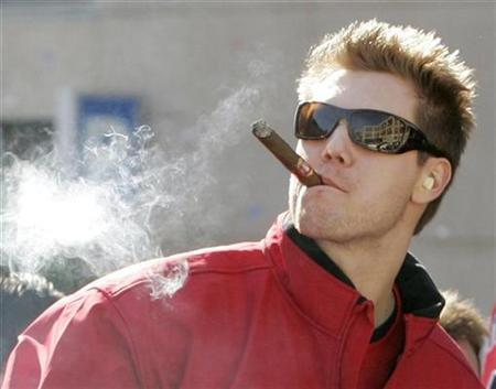 Boston Red Sox's relief pitcher Jonathan Papelbon puffs on a cigar in Boston, Massachusetts, October 30, 2007. Altria Group said on Thursday it would acquire cigar maker John Middleton Inc for $2.9 billion. REUTERS/Steven Senne/Pool (UNITED STATES)