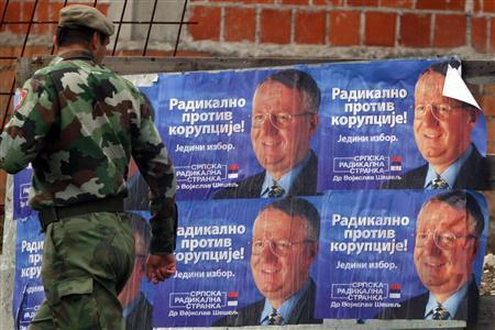 A soldier looks at Radical Party posters with photos of its leader and war crimes suspect Vojislav Seselj in the Bosnian Serb capital Banja Luka, September 27, 2006. Seselj, the leader of Serbia's ultranationalist Radical Party, went on trial on Wednesday accused of stirring up hatred of Croats, Muslims and other non-Serbs and inciting murder, torture and persecution. REUTERS/Ranko Cukovic