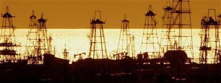 Oil derricks are silhouetted against the rising sun at an oilfield in the capital Baku October 16, 2005. Oil will breach the $100 barrier, but this will not kill off global economic growth, the head of Germany's Deutsche Bank said at the Reuters Finance Summit. REUTERS/David Mdzinarishvili