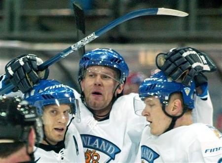 Finland's Jere Karalahti (C) celebrates his goal with team mates Kimmo Timonen (L) and Jukka Hentunen during their opening Group C match with Denmark at the Ice Hockey World Championship in Innsbruck, Austria April 30, 2005. Karalahti has been arrested in his native Finland on suspicion of a drugs crime, police said on Friday. REUTERS/Dominic Ebenbichler