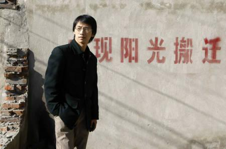 Zhou Shuguang, whose amateur reporting of a famous property dispute lead to him being hailed as China's ''first citizen reporter'', poses in front of a dismantled house in Beijing November 2, 2007. REUTERS/Jason Lee