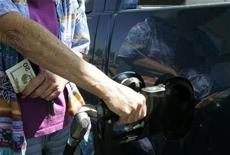 A customer clutching $20 bills pumps gas at a Phillips 66 gas station in Centennial, Colorado June 26, 2006. U.S. consumers could pay record gasoline prices for the upcoming Thanksgiving holiday with pump costs expected to climb another 20 cents over the next two to three weeks, the government's top energy forecaster warned on Monday. REUTERS/Rick Wilking