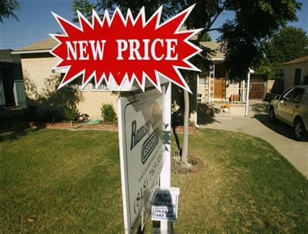 A real estate sign, which indicates the 'new price', stands outside a three-bedroom and one-bath home in Burbank, California October 9, 2007. The U.S. housing market's skid is nowhere near over and could extend for another five or even 10 years, according to one of the most-watched housing economists. REUTERS/Fred Prouser