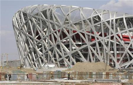 Construction workers walk in front of the construction site of the Olympic stadium in Beijing November 8, 2007. The main stadium for next year's Beijing Olympic Games, the $400 million ''bird's nest'', will open to the public for the first time in April to host a test event, a state newspaper said on Thursday. REUTERS/Reinhard Krause